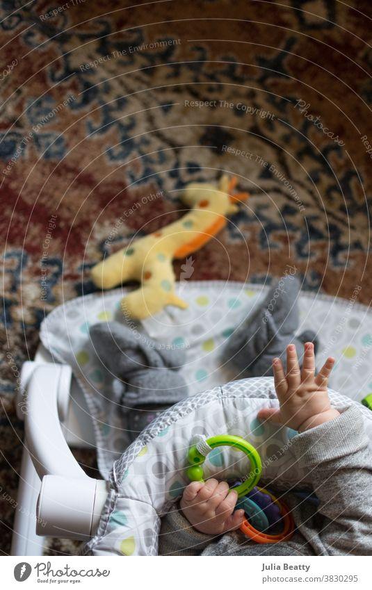 Baby sitzend mit Spielzeug auf orangem Teppich; nach Giraffenspielzeug greifend Säugling Kind 0-12 Monate Kindheit Kunststoffringe Schühchen Tropfen