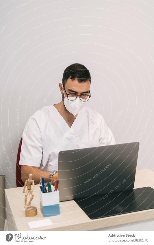 Seriöser Arzt im Krankenzimmer im Krankenhaus Mann Arbeit Laptop medizinisch Mundschutz Raum Klinik Tippen arzt männlich beschäftigt Beruf Spezialist Gerät