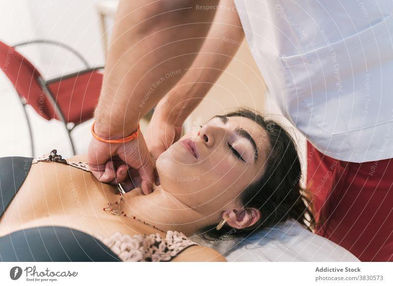 Männlicher Therapeut bei der Behandlung eines Klienten in der Klinik Physiotherapie Leckerbissen Arzt geduldig Tisch medizinisch Verfahren Gesundheitswesen