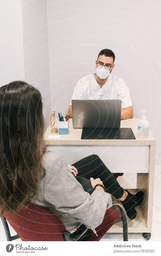 Ernster Arzt mit Patient im medizinischen Raum im Krankenhaus Mann geduldig Arbeit Laptop Mundschutz Klinik Tippen arzt männlich beschäftigt Beruf Spezialist