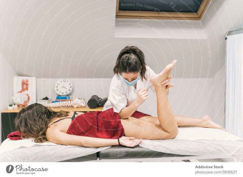 Physiotherapeut streckt das Bein eines Patienten im medizinischen Raum Rehabilitation Dehnung Physiotherapie Hilfsbereitschaft geduldig Therapeut Therapie