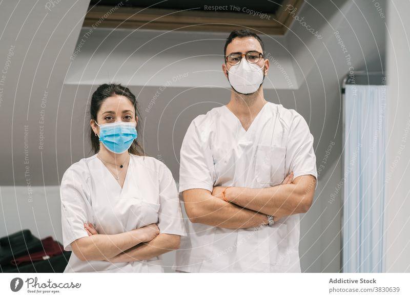 Lächelnde Ärzte in Uniform und Maske schauen in die Kamera Arzt Sanitäter Krankenhaus Personal heiter Beruf Spezialist professionell medizinisch stehen Dienst
