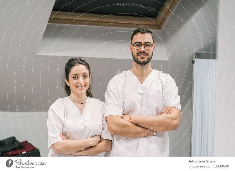 Lächelnde Ärzte in Uniform schauen in die Kamera Arzt Sanitäter Krankenhaus Personal heiter Beruf Spezialist professionell medizinisch stehen Dienst Medizin