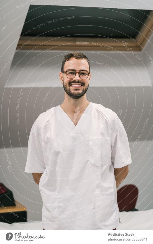 Fröhlicher Arzt in Uniform im medizinischen Raum weiß Kleid Mann heiter Personal Klinik Büro männlich Medizin Job modern Spezialist Lächeln Leckerbissen