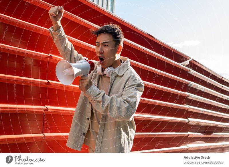 Emotionaler asiatischer Mann, der in den Lautsprecher schreit und die Faust hebt Schrei schreien Megaphon auflehnen revolutino emotional überwältigt rühren