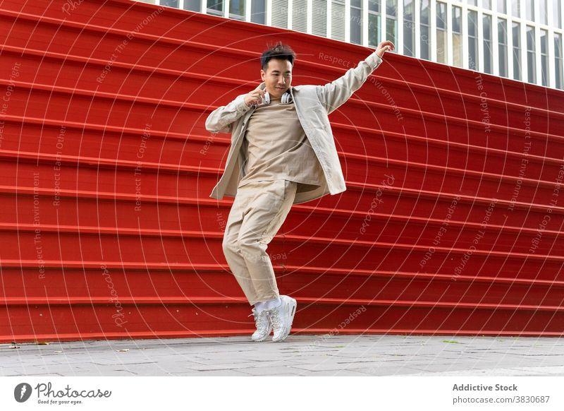 Erfreut asiatischen Mann hören Musik in Kopfhörer in der Nähe von Straße Zaun genießen freudig Spaß Lachen Freude zuhören schlendern Audio unterhalten Headset
