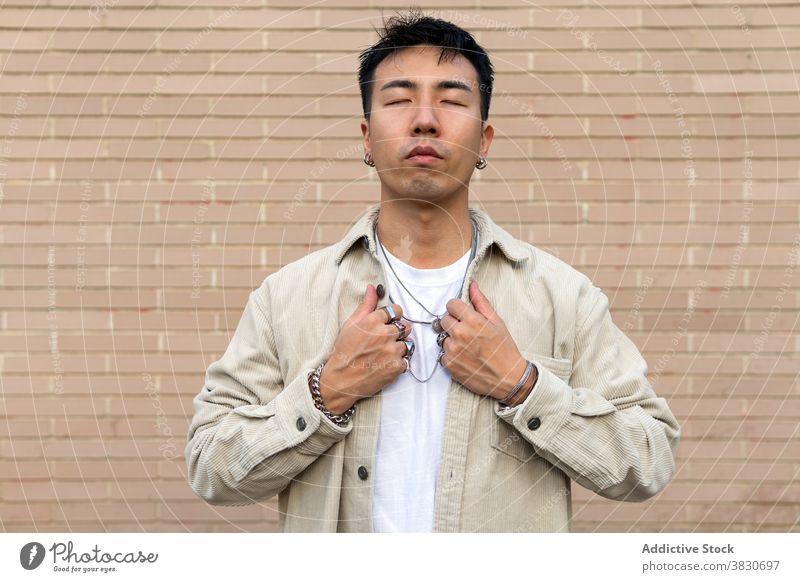 Nachdenklich asiatischen Mann stehend mit geschlossenen Augen gegen Backsteinmauer nachdenken Augen geschlossen Windstille emotionslos berühren Revers