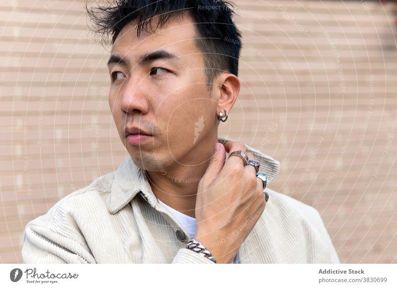 Nachdenklich asiatischen Mann stehend mit geschlossenen Augen gegen Backsteinmauer nachdenken Windstille emotionslos berühren Revers nachdenklich ernst