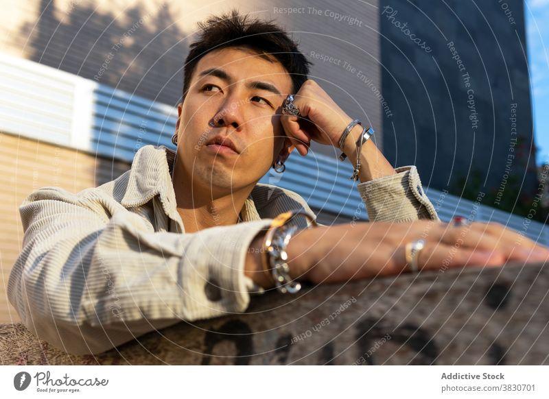 Nachdenklicher asiatischer Mann lehnt sich mit der Hand an ein Backsteingebäude nachdenklich besinnlich sich auf die Hand lehnen ruhen Windstille nachdenken