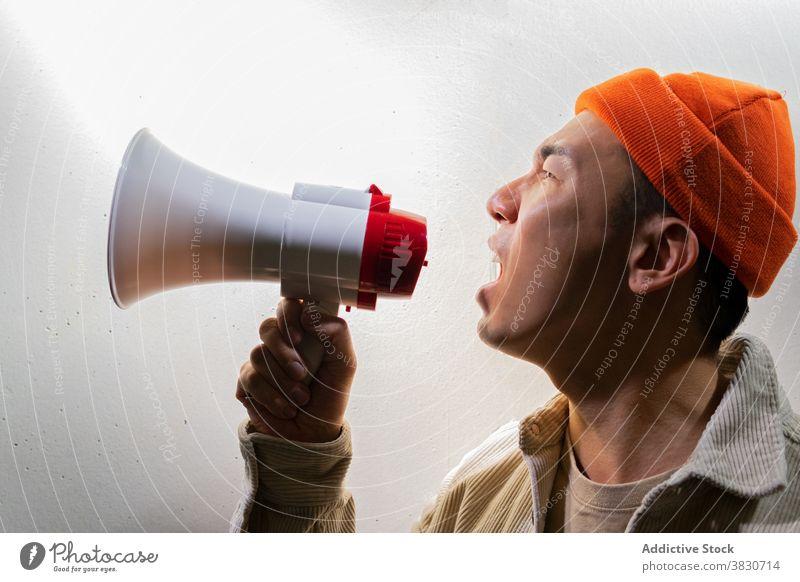 Ausdrucksstarker Mann schreit in Megaphon gegen graue Wand Schrei schreien überwältigt expressiv Lautsprecher Dunkelheit Emotion ausrufen Stimme Schreien Sie