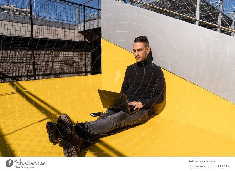 Junger Mann surft auf dem Laptop, während er draußen arbeitet Tippen Inbetriebnahme benutzend Fokus Konzentration ernst beschäftigt Browsen männlich online