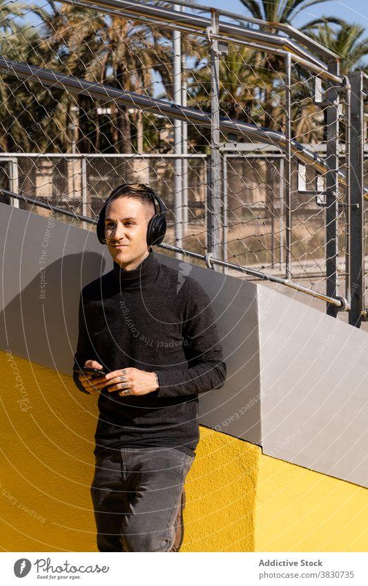 Selbstbewusster Mann in der Nähe der Wand, der mit Kopfhörern Musik hört benutzend Smartphone Hobby zuhören Drahtlos Gesang Wiedergabeliste männlich Gerät Audio