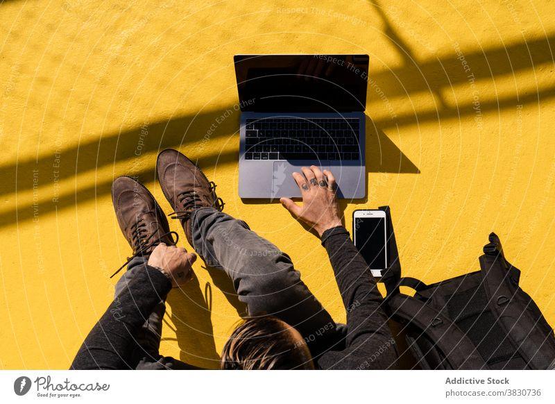 Mann mit Laptop und Smartphone auf Holzbank Gespräch Anruf Kommunizieren abgelegen freiberuflich benutzend Kopfhörer männlich Gerät Inbetriebnahme Tippen