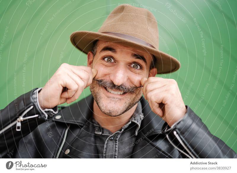 Fröhlicher Mann mit Schnurrbart im Hut und Grimasse Locken Gesicht machen Spaß heiter Lederjacke männlich froh Lächeln so tun, als ob Metrosexualität Optimist