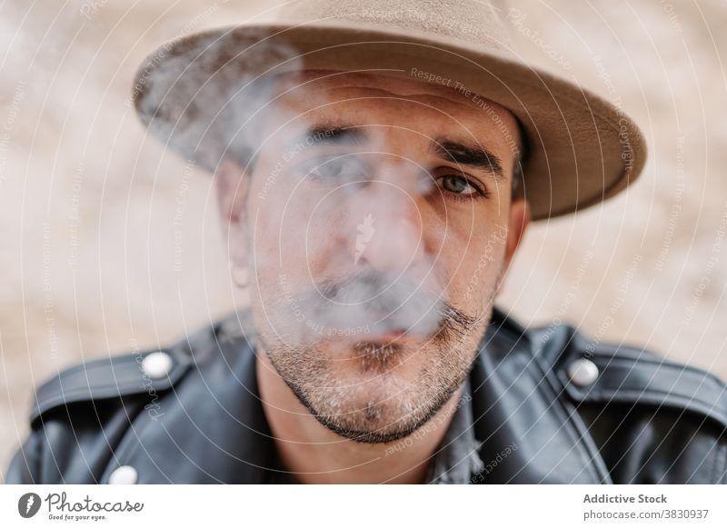 Ernster, nachdenklicher Mann mit Hut, der raucht cool Rauch Zigarette Schnurrbart Hipster brutal ruhen nachdenken männlich friedlich modern selbstbewusst