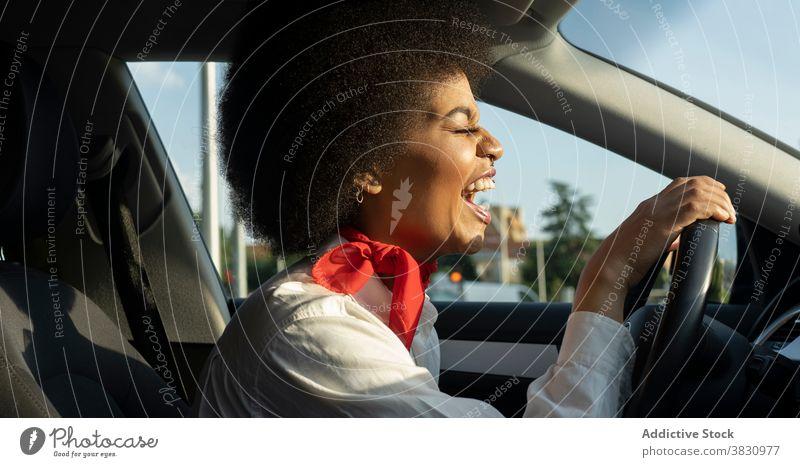 Glückliche schwarze Frau fährt Auto und lächelt hell aufgeregt Laufwerk PKW Augen geschlossen Lachen froh Freude Optimist heiter sich[Akk] entspannen Automobil