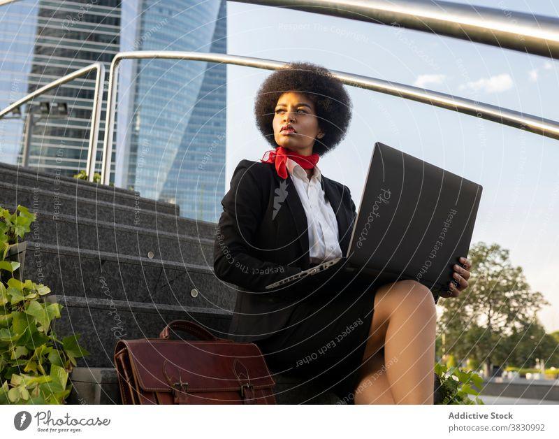 Schwarze Geschäftsfrau arbeitet an Laptop auf Stufen benutzend Unternehmer ernst Kommunizieren abgelegen Frau Exekutive Anschluss Gerät Konzentration Apparatur