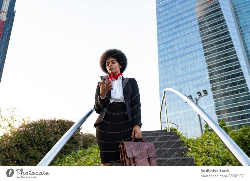 Schwarze Geschäftsfrau auf Smartphone Frau selbstbewusst Anruf benutzend Unternehmer zuhören formal Gespräch Exekutive Business Aktentasche ernst Telefon Mobile