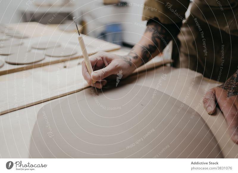 Crop-Keramikerin stellt in ihrer Werkstatt handgefertigte Tonwaren her kreieren Kunstgewerbler Töpferwaren Steingut Material Werkzeug stechend Spielfigur