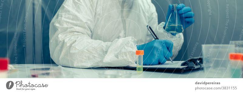 Wissenschaftlerin mit Schutzanzug untersucht im Labor bakteriologischer Schutzanzug Reagenzglas Virus Coronavirus mitschreibend Impfstoff Fundstück Transparente