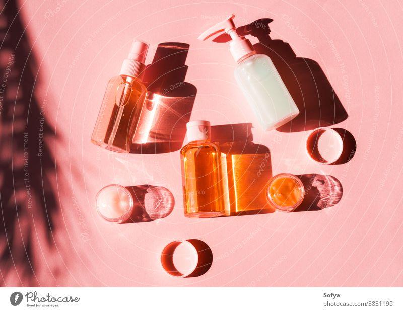 Verschiedene kosmetische Produkte auf rosa Koralle. Flach gelegt Haut Schatten flache Verlegung Kosmetik orange Sahne Korallen Pflege golden gelb Morgen Lotion