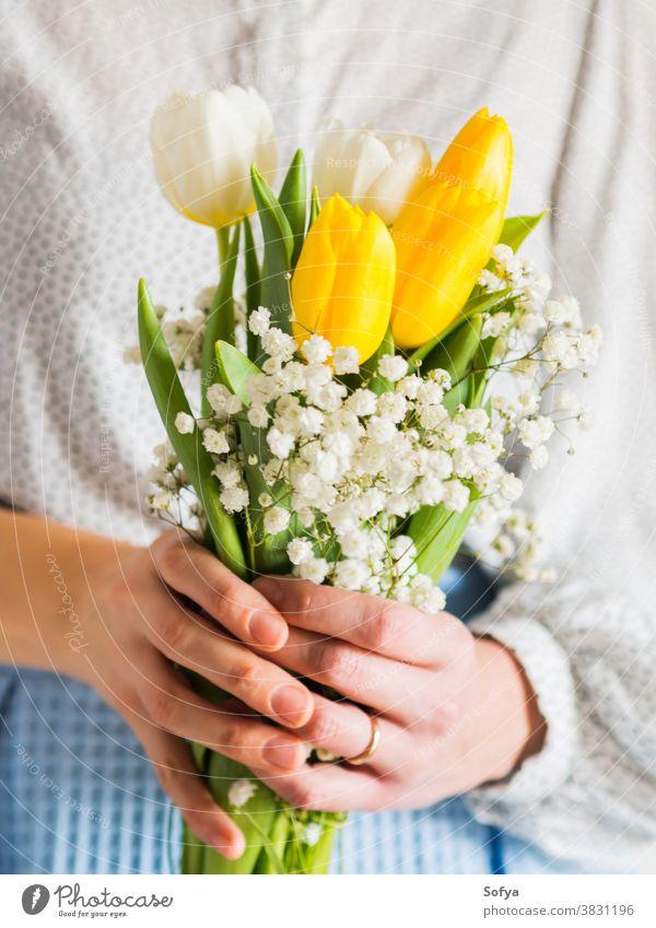 Frau hält Tulpenstrauß. Der Tag der Frau Blumenstrauß Hintergrund Hände Mutter Ostern schön März Haufen Postkarte festlich geblümt Geschenk geben Gruß