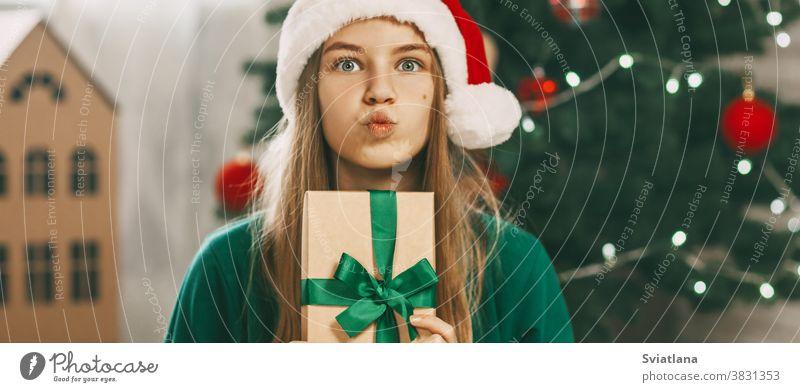 Ein schönes Mädchen mit überraschten Augen schaut in die Kamera mit einem Geschenk aus Kraftpapier, das mit einem grünen Band gebunden ist. Weihnachtsstimmung. Konzept für den Neujahrsfeiertag zu Hause.