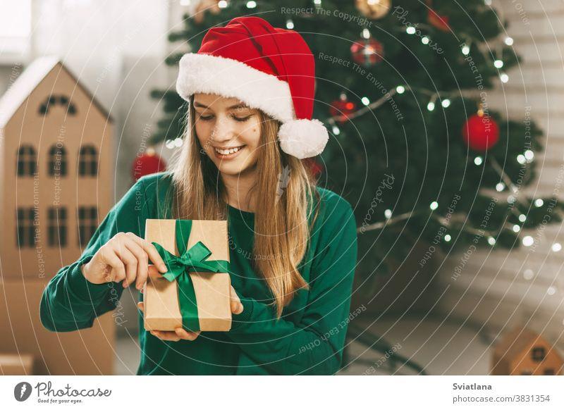 Hübsche Teenagerin öffnet ein Geschenk aus Kraftpapier, das mit einem grünen Band gebunden ist, Neujahrsstimmung. Feiertagskonzept von Weihnachten und Neujahr zu Hause.