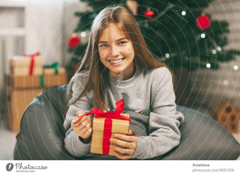 Hübsche Teenagerin öffnet ein Geschenk aus Kraftpapier, das mit einem roten Band gebunden ist, Neujahrsstimmung. Feiertagskonzept von Weihnachten und Neujahr zu Hause.