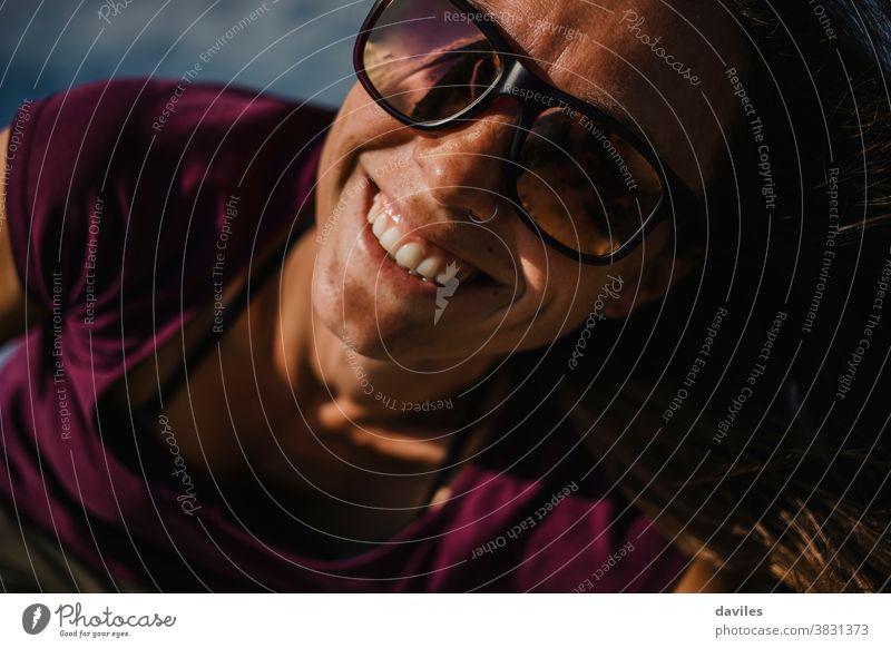 Nahaufnahme einer Frau mit Sonnenbrille, die in die Kamera schaut, im Freien an einem sonnigen Tag. niedlich Nizza Zähne weiß braun Haut Nase Piercing Ausdruck