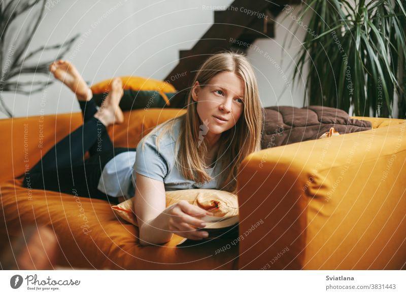 Ein schönes Mädchen entspannt sich auf dem Sofa im Wohnzimmer und liest ihren Lieblingsroman. Ein süßes, nachdenkliches Mädchen liegt auf dem Sofa und liest ein Buch.