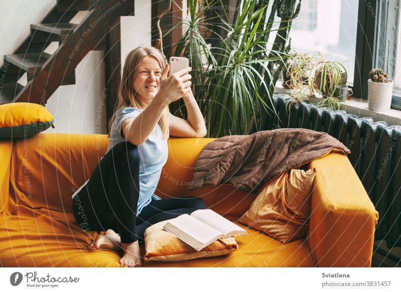 Ein junges Mädchen sitzt auf dem Sofa und telefoniert mit einem Selfie, neben ihr liegt ein offenes Buch heimwärts Frau Funktelefon Raum Telefon Drahtlos Text