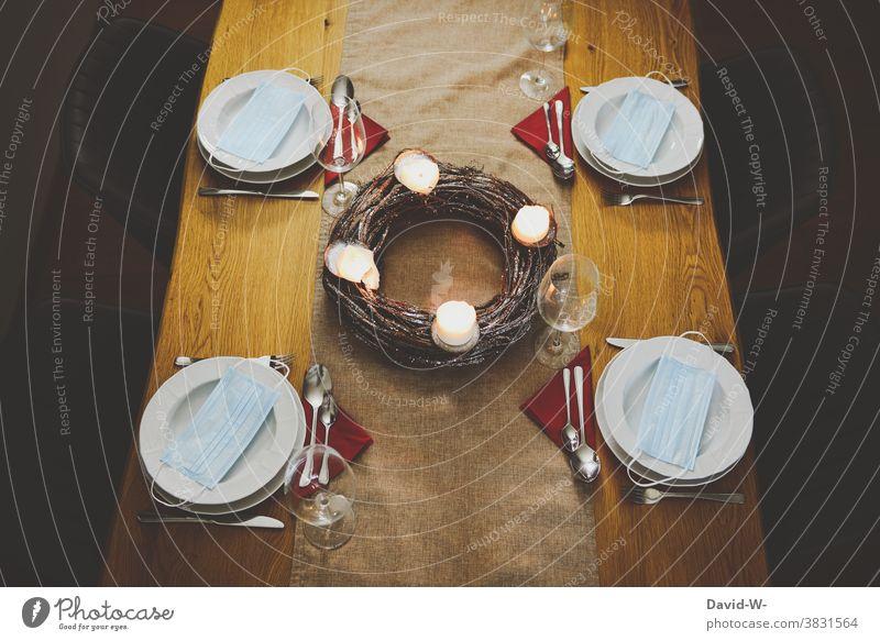 Corona Weihnachtsessen - festlich gedeckter Tisch an Weihnachten Masken Mundschutz Abstand Pandemie Regeln Heiligabend Infektionsgefahr Gesundheit Coronavirus