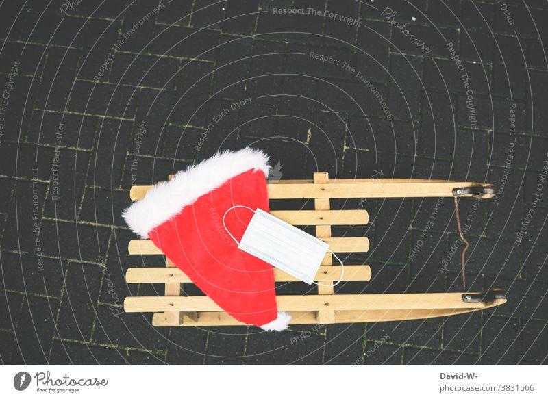 Schlitten mit Nikolausmütze und Atemschutzmaske / Mundschutz Corona Weihnachten pandemie Coronavirus Schützen