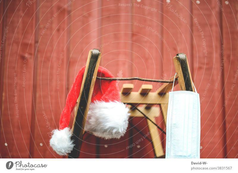 Winterzeit - Schlitten und Nikolausmütze und immer dabei der Mundschutz / Atemschutzmaske Weihnachten Corona Pandemie coronavirus schützen Coronavirus