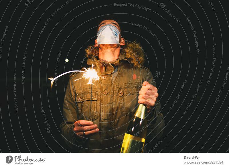 Mann mit Mundschutz / Atemschutzmaske steht an Silvester draußen und hält eine Wunderkerze und Sektflasche in den Händen Corona Coronavirus Neujahr Zukunft 2021