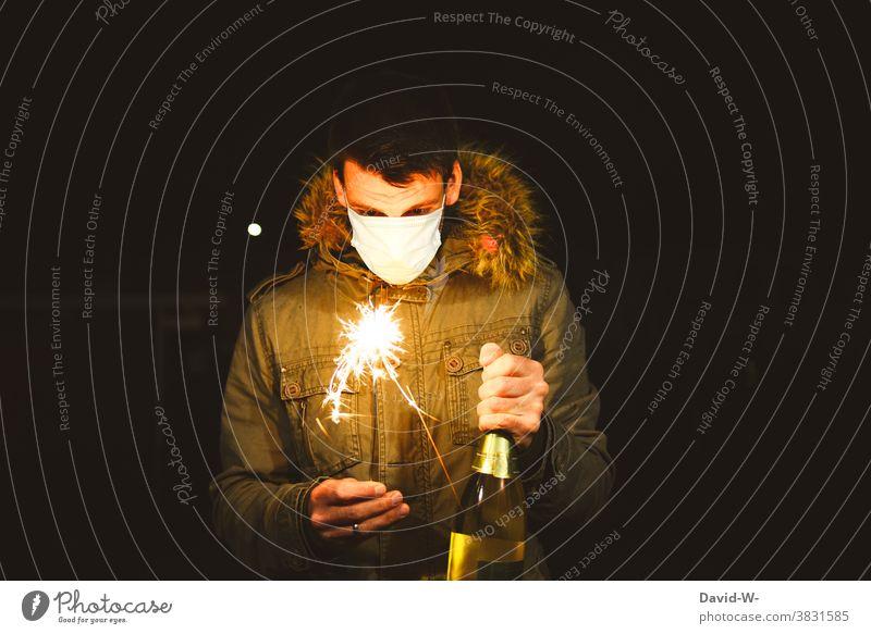 Silvester und Corona - Mann mit Mundschutz / Atemschutzmaske und Wunderkerze Silvester u. Neujahr leuchten feiern alleine einsam Quarantäne coronavirus Sekt
