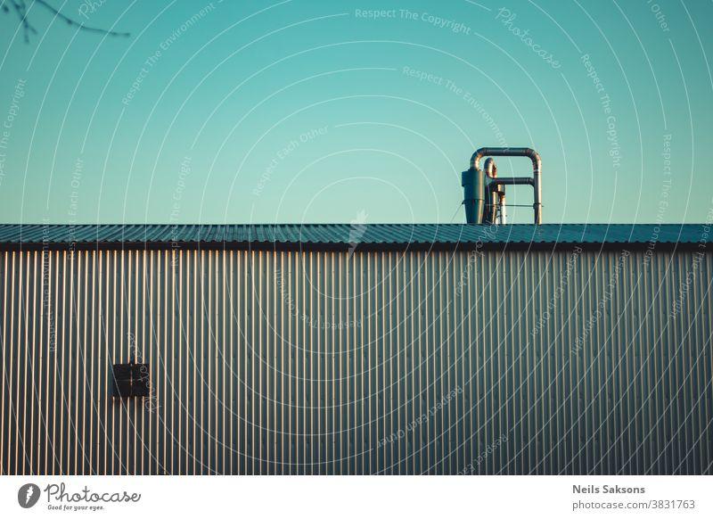 Wandpaneele aus Metallblech und Dach mit Rohren gegen klaren blauen Himmel Metalldach abstrakt gealtert Leichtmetall Architektur Hintergrund gebaute Struktur