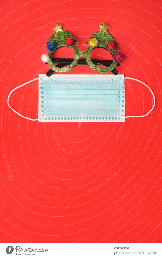 Fröhliche Weihnachten.Weihnachtskonzept Hintergrund.Weihnachtsbrille mit chirurgischer Schutzmaske Weihnachtsmann Coronavirus Weihnachtsgläser