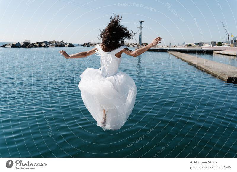 Anonyme Frau im Brautkleid fällt ins Wasser weißes Kleid hochzeitlich fallen Strandpromenade See Pier jung aufgeregt ertrinken Spaß flippig Stauanlage ängstlich