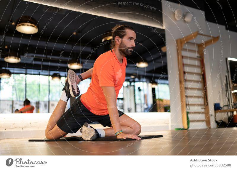 Bärtiger Sportler beim Stretching in der Turnhalle Training Dehnung Fitness Fitnessstudio beweglich modern Stock Gesundheit passen männlich Athlet Erwachsener