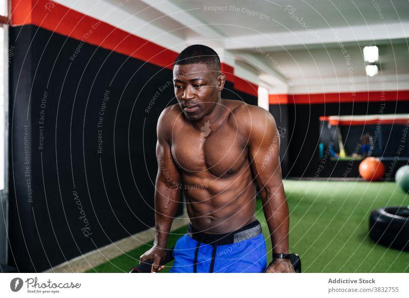 Muskulöser schwarzer Mann macht Trizepsübungen am Barren Übung Fitnessstudio Sportler parallel Athlet Training operativ männlich ethnisch Afroamerikaner Kraft