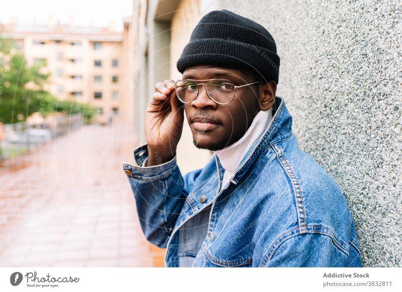 Stilvoller schwarzer Mann auf der Straße Brille angezogen Jeansstoff Outfit Jacke trendy jung männlich ethnisch Afroamerikaner Großstadt modern selbstbewusst