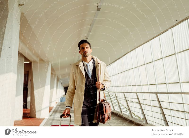 Stylish Mann zu Fuß entlang Flughafen ernst selbstbewusst Stil Koffer besinnlich nachdenklich Gang Gepäck männlich ethnisch Spaziergang modern Abheben Tasche