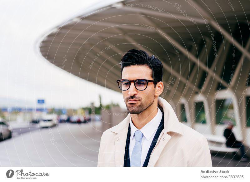 Nachdenklich junger Mann steht auf der Straße in der Nähe von modernen Gebäude besinnlich nachdenklich ernst Windstille ruhig Stil trendy Geschäftsmann männlich