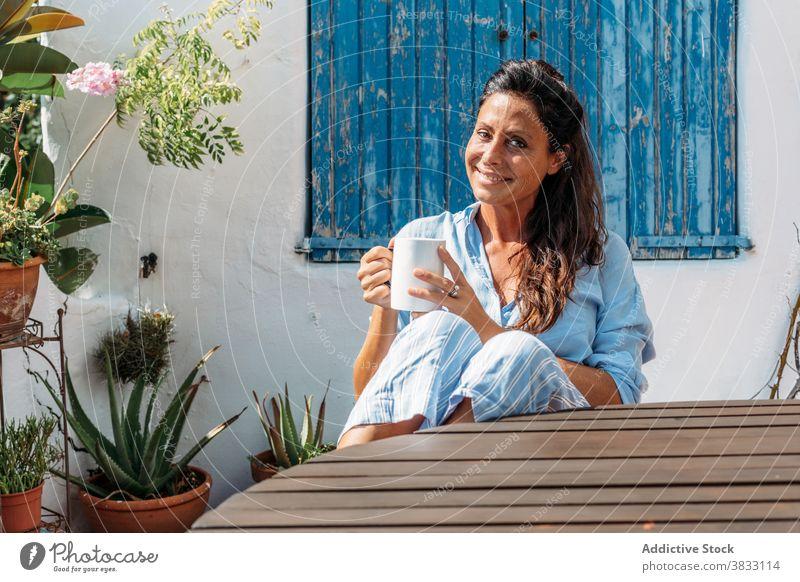 Lächelnde Frau trinkt Kaffee auf der Terrasse Glück heiter ruhen trinken Tasse Erwachsener ethnisch Getränk Optimist froh sich[Akk] entspannen Lifestyle Pause