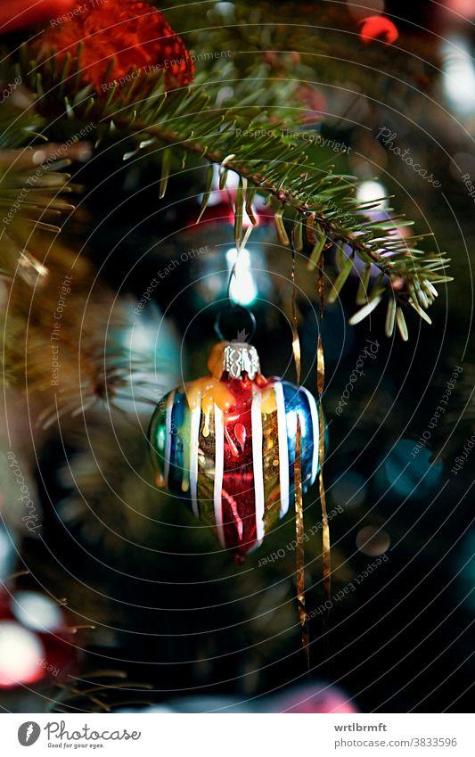 Ein Detail eines klassischen deutschen Weihnachtsbaums mit echten Kerzen und viel Lametta und einem herzförmigen Weihnachtsschmuck. Weihnachten Ornament