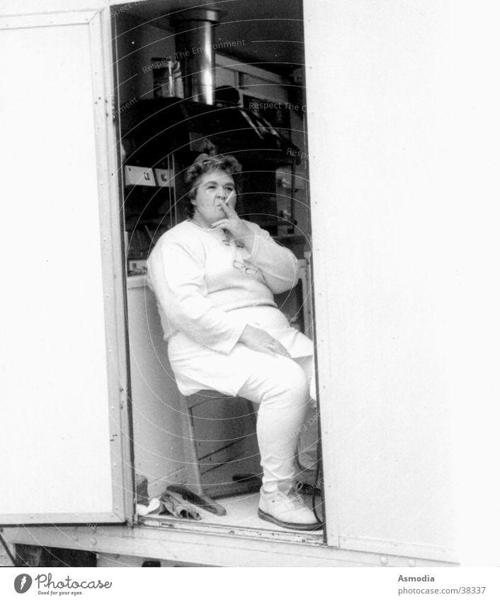 Pommesfrau Frau weiß schwarz sitzen Pause Stuhl Rauchen Übergewicht dick Zigarette Arbeitsplatz Koch ungesund Imbiss Kittel Arbeitspause