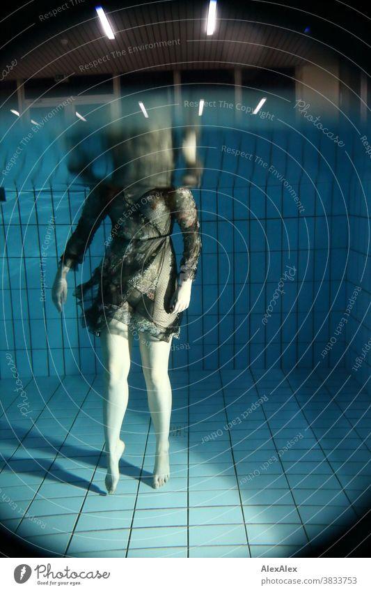 Körperportrait einer jungen Frau unter Wasser, die in einem Pool steht und mit einem durchsichtigen Kleid bekleidet ist und badet junge Frau blass unterwasser
