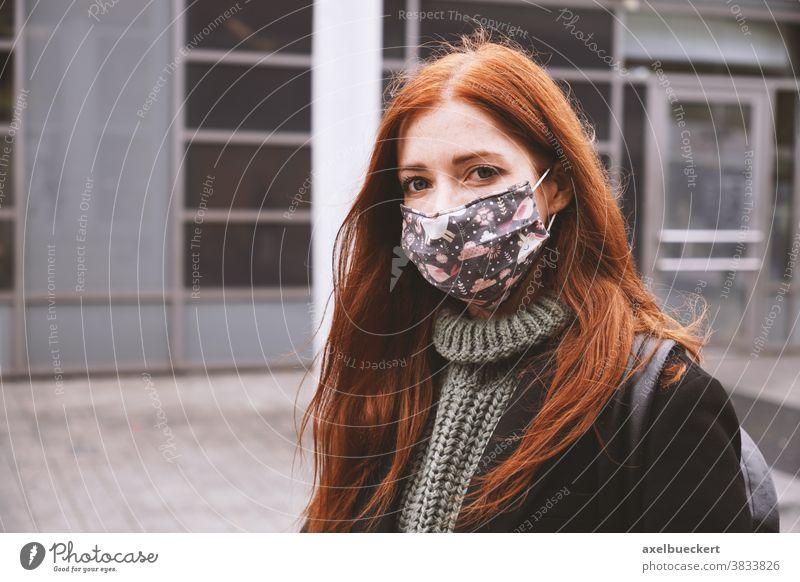 junge Frau, die in der Stadt draußen eine selbstgemachte Alltagsmaske trägt Stoffmaske Stoffgesichtsmaske Mund-Nasen-Bedeckung Corona Lifestyle Winter